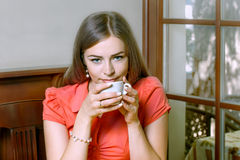 Girl with blue eyes dressed in red blouse drinking coffee Royalty Free Stock Photos