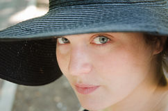 Girl with blue eyes and hat. Girl with hat in park on summer day Royalty Free Stock Image