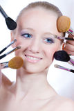 Girl with blue eyes and makeup brushes. Beautiful young blond girl with blue eyes and makeup brushes on white stock photo