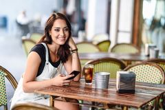 Girl with blue eyes sitting on urban cafe using smart phone smiling. Happy woman with brown wavy hairstyle wearing white denim dress. Lifestyle concept stock photos