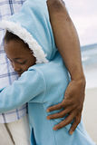 Girl (7-9) in blue fleece with hood embracing father on beach, smiling, eyes closed, close-up royalty free stock photos
