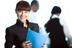 Girl with blue folder and men and women. Girl with smile with blue folder and men and women stock photo