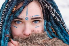 A girl with blue hair dreadlocks. Face painted with watercolors close up stock image