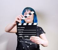 A girl with blue hair, holding a clapper. royalty free stock images
