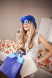 Girl in a blue hat and glasses with bags Stock Images