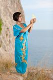 Girl in blue indian dress on seacoast. Girl in blue indian dress with origami on seacoast Royalty Free Stock Photo