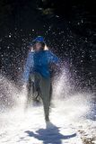 Girl in a blue jacket with hood kicking snow on a sunny day stock photography