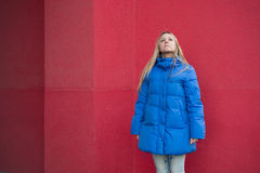 Girl in blue jacket stands on the background of a pink wall Royalty Free Stock Photos