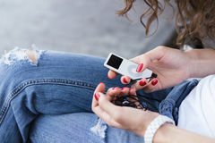 Girl in blue jeans holding a music player in hands with a red ma Stock Image