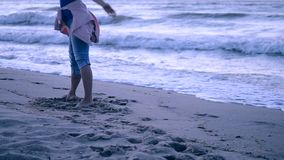 A girl in blue jeans and a pink jacket tied on her belt came to the sea stock footage