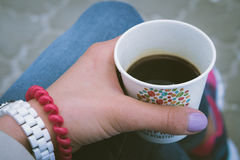 Girl in blue jeans resting and drinking coffee outdoor. S. Disposable coffee cup in a female hand with bracelets closeup. Point of view shot Royalty Free Stock Image