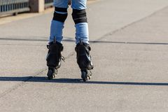Girl in blue jeans rollerblading. Roller skating rear view royalty free stock image