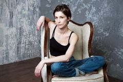 The girl in blue jeans sitting in an armchair on a dark blue background royalty free stock images