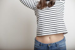Girl in blue jeans and a striped sweater and lifted her arms bar. Young girl in blue jeans and a striped sweater and lifted her arms bare belly with a beautiful Royalty Free Stock Images