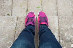 Girl with blue jeans and sweet pink shoes standing on cement floor. Young girl with blue jeans and sweet pink shoes standing on cement floor Royalty Free Stock Photos