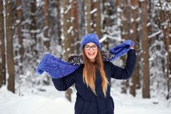 Girl in blue knitted scarf with hat in winter forest. Girl in blue knitted scarf with hat in winter forest Stock Image