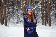 Girl in blue knitted scarf with hat in winter forest. Girl in blue knitted scarf with hat in winter forest Stock Photos