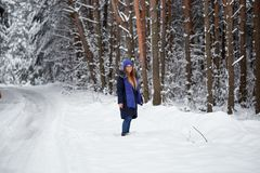 Girl in blue knitted scarf with hat in winter forest. Girl in blue knitted scarf with hat in winter forest Stock Photo