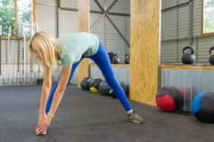 Girl in blue leggings in the gym on the background of sports equipment medical balls,dumbbells and bars,makes the exercise leans stock photos