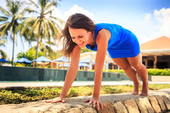 Girl in blue lies stretching arms in elbows on stone barrier Stock Image
