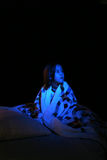 Girl with blue light as  if from TV Royalty Free Stock Photos