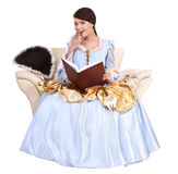 Girl in blue lond dress with book on chair. Isolated Royalty Free Stock Images