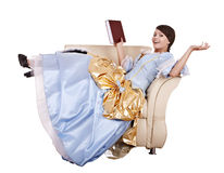 Girl in blue lond dress with book on chair. Isolated Stock Photography