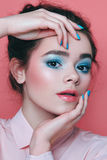 Girl with blue makeup, with blue nails on a pink background. Portrait. the girl's face Royalty Free Stock Photography
