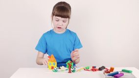 Girl in blue molds house from plasticine on white table in white room, time lapse stock video footage