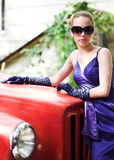 Girl in blue near red car Royalty Free Stock Photos