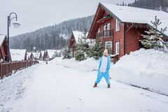 Girl in blue, pink unicorn pijama kigurumi outdoor in front of the wood houses on the ski report in snow mountains. stock photos