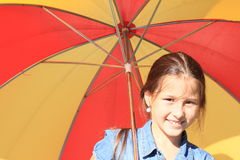 Girl in blue with red and yellow umbrella Royalty Free Stock Photo