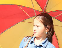 Girl in blue with red and yellow umbrella Stock Photo