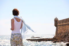 Girl with a blue scarf on seashore Stock Photo