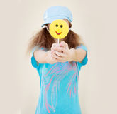 Girl in blue shirt and cap with two tails holds in front of a big yellow candy Royalty Free Stock Image