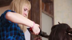 Girl curls her friend`s hair with a Curling iron stock video
