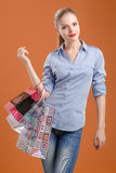 Girl in a blue shirt and jeans with shopping bags Royalty Free Stock Images