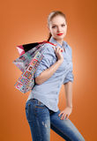 Girl in a blue shirt and jeans with shopping bags Royalty Free Stock Image