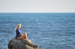 Girl in the blue shirt looks at the sea Royalty Free Stock Photo
