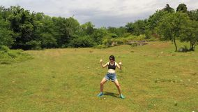 Girl in blue shorts performing exercises and crazy dance moves. Aerial drone view. Girl in blue shorts and black sunglasses standing on green lawn with lush stock video footage