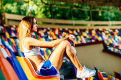 Girl in blue shorts sitting on stadium Stock Image