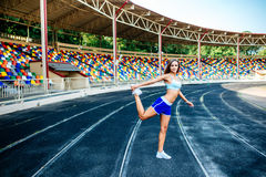 Girl in blue shorts workout on stadium Stock Photos