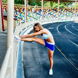 Girl in blue shorts workout on stadium Royalty Free Stock Photography