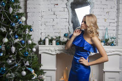 Girl in blue silk dress near new year tree Royalty Free Stock Photos