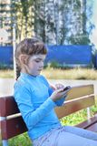 Girl in blue sits with smartphone on bench Stock Photo