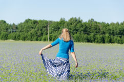Girl with blue skirt dance in cornflower meadow Royalty Free Stock Photos