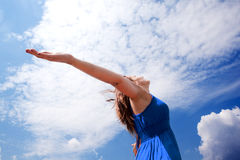 Girl and blue sky. Girl with open arms to the sky royalty free stock photo