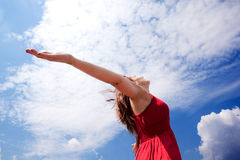 Girl and blue sky. Girl with open arms to the sky royalty free stock image