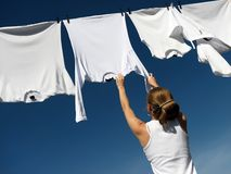 Girl, Blue Sky And White Laundry Royalty Free Stock Photos