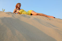 Girl in the blue sky lies on sand. The beauty with red hair in a yellow dress against the blue sky lies on sand on a sunset Stock Photography